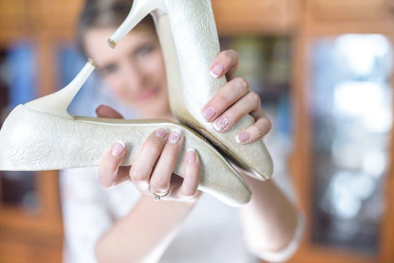关闭拿着婚礼鞋子在形式心脏的逗人喜爱的新娘女孩画象在她的手上 免版税库存图片