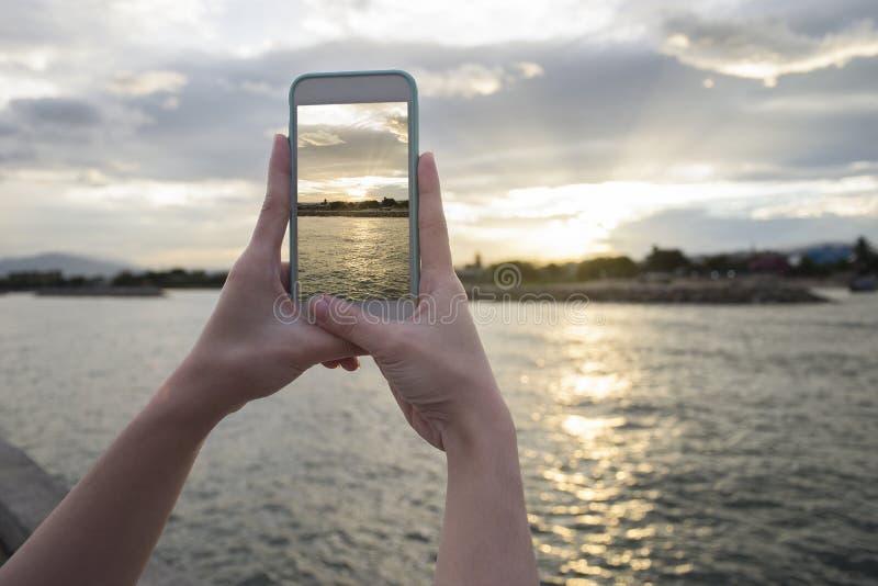 关闭拿着巧妙的电话,机动性,在被弄脏的美丽的海的巧妙的电话的妇女的手有日落片刻的采取pho 图库摄影