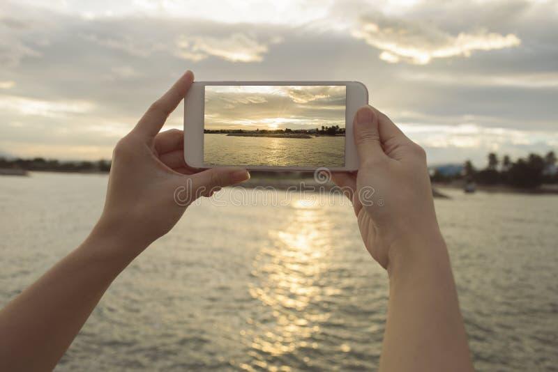 关闭拿着巧妙的电话,机动性,在被弄脏的美丽的海的巧妙的电话的妇女的手有日落的拍照片 免版税库存照片