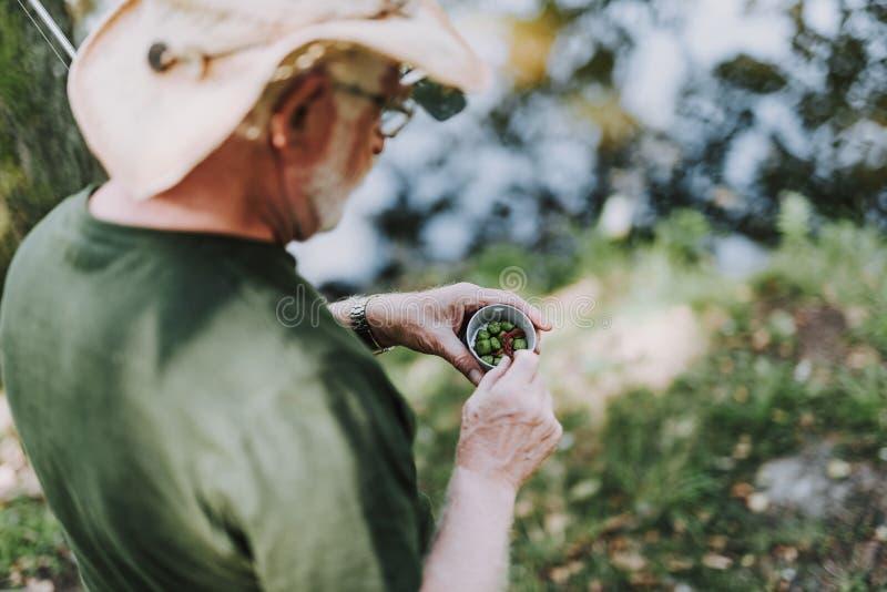 关闭拿着有诱饵的一个年迈的钓鱼者一个箱子 免版税库存照片