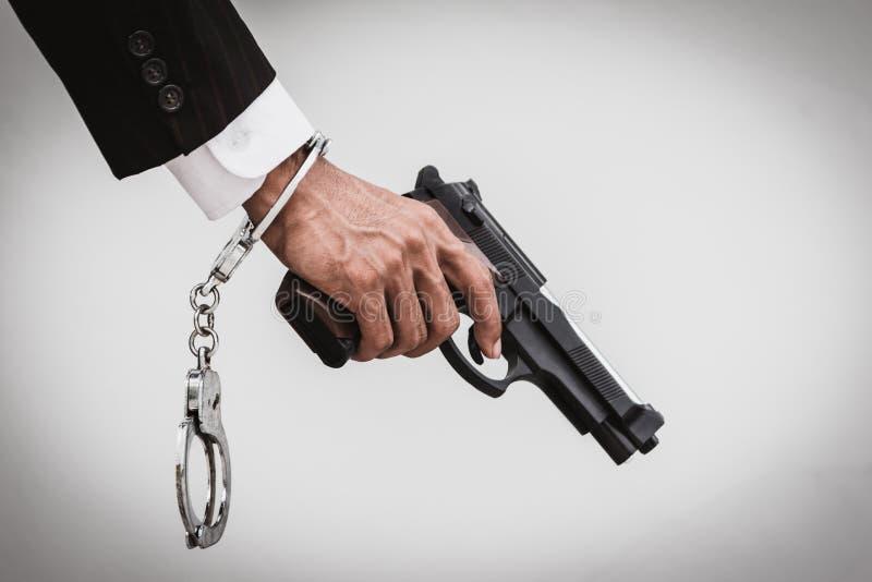 关闭拿着枪和手铐的西装的人 免版税库存照片