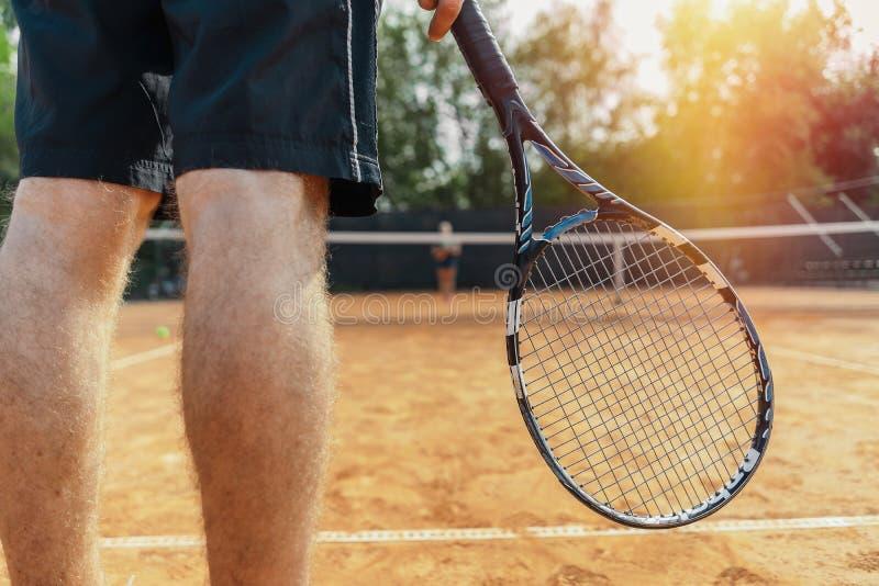 关闭拿着球拍的人,当等待球服务在网球场时 免版税库存图片