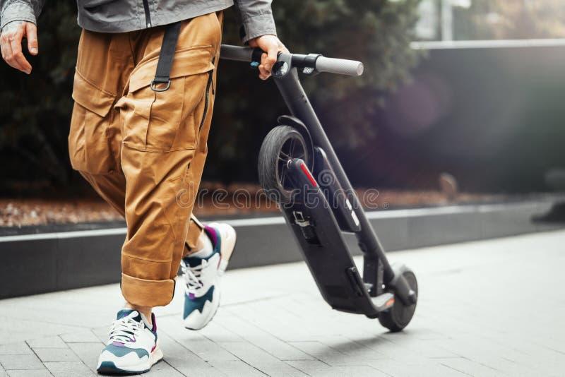 关闭拿着电反撞力滑行车的人,当散步在街道时 库存照片