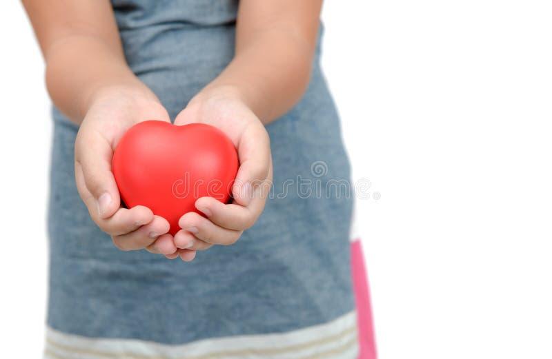 关闭拿着红色心脏的儿童手 库存图片