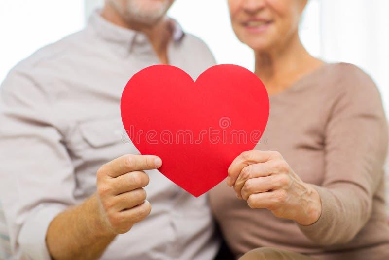 关闭拿着红色心脏的愉快的资深夫妇 免版税库存图片