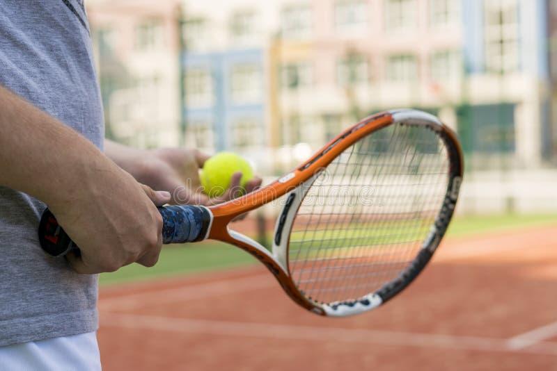 关闭拿着网球和球拍的年轻人 免版税库存照片