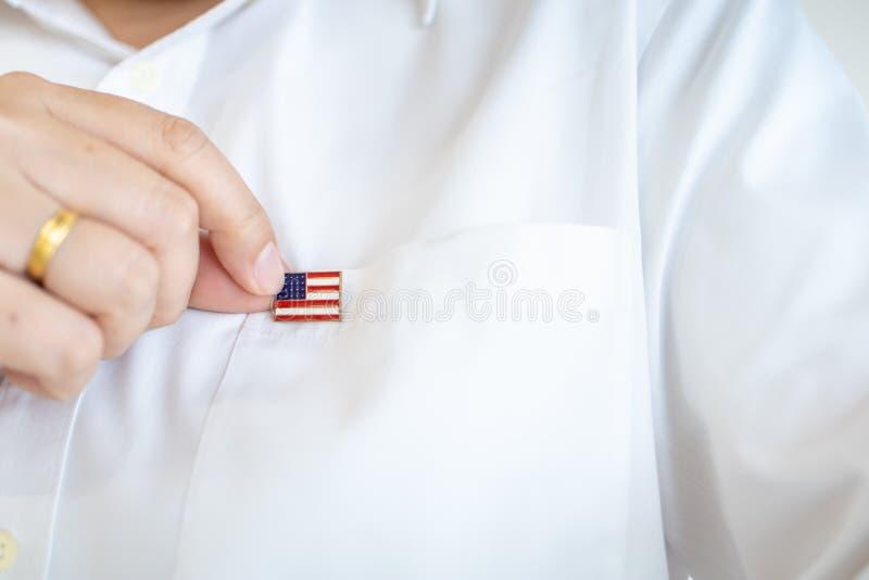 关闭拿着美国国家在白色衬衫旗子的旗子别针的团结的状态人手 免版税库存图片