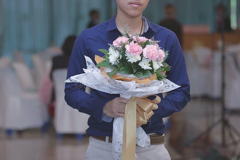 关闭拿着花的美丽的花束他的女朋友的英俊的年轻人 甜华伦泰` s天或婚礼概念 免版税库存照片
