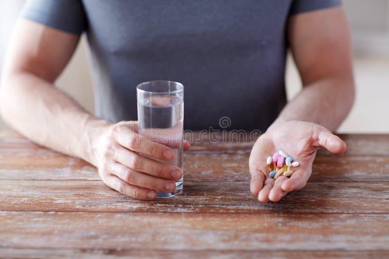 关闭拿着药片的男性手并且浇灌 库存图片
