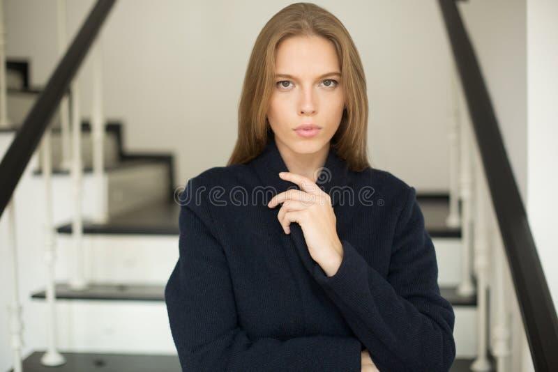 关闭拿着衣领在她的手上的外套的可爱的女孩 免版税库存图片