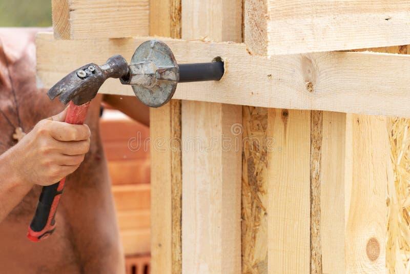 关闭拿着金属锤子在手上的手击中在板条板的金属元素在木杆建筑工作员的播种的照片  免版税图库摄影