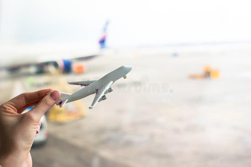 关闭拿着飞机模型的手在机场 库存照片