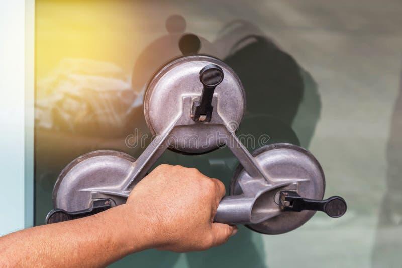 关闭拿着玻璃吸杯子板材工具的手玻璃剪裁工 库存照片