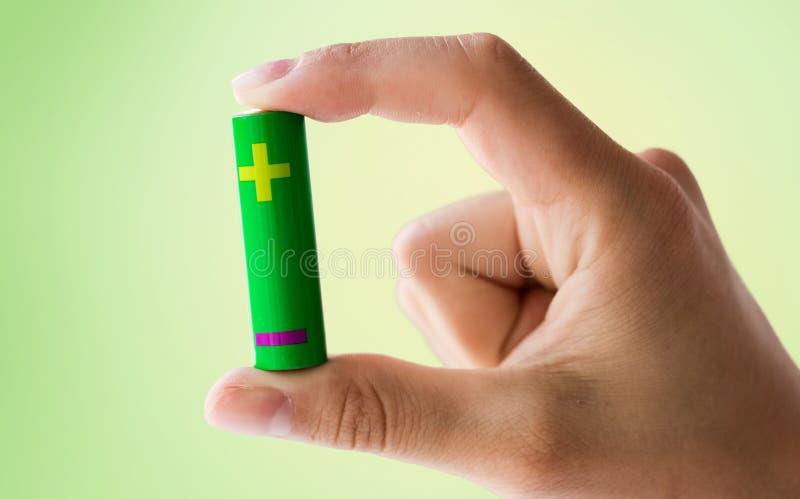 关闭拿着绿色碱性电池的手 免版税图库摄影