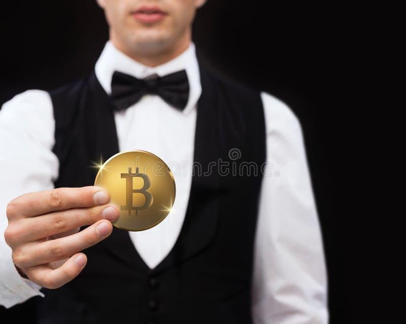关闭拿着bitcoin的赌博娱乐场经销商 免版税图库摄影