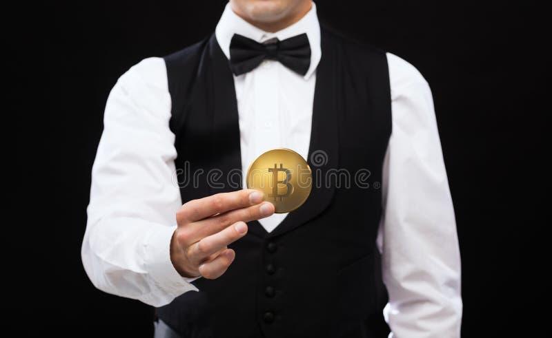 关闭拿着bitcoin的赌博娱乐场经销商 库存图片