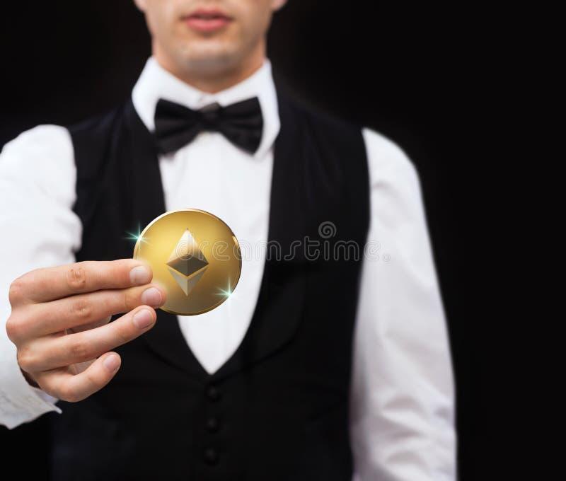 关闭拿着ethereum硬币的赌博娱乐场经销商 免版税库存照片