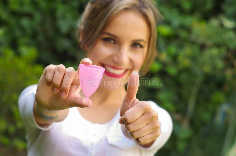 关闭指向在她前面一个月经杯子在一只手,妇科学概念, ith上的一个少妇她的thums  免版税图库摄影