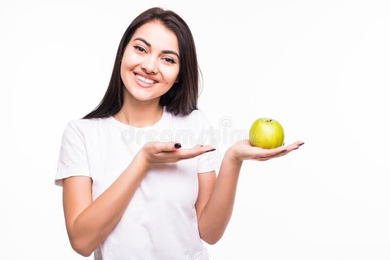 关闭指向在她的棕榈的一个苹果的一个爽快愉快的女孩在白色背景 免版税库存照片