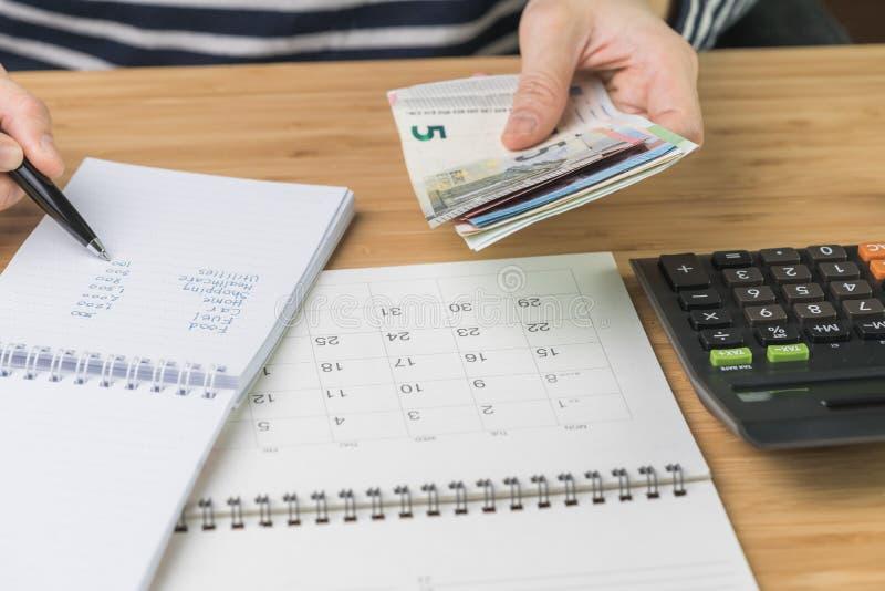 关闭指向在预算、费用和费用名单上的妇女手拿着金钱的和其他手候宰栏在小笔记薄与 库存图片