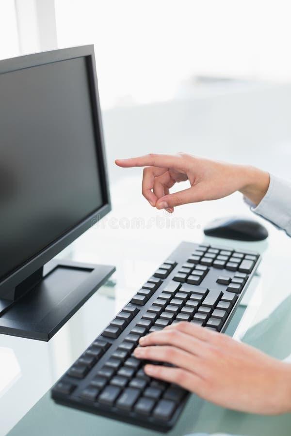 关闭指向她的有她的手指的屏幕的女实业家 免版税库存照片