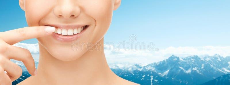 关闭指向牙的微笑的妇女面孔 图库摄影