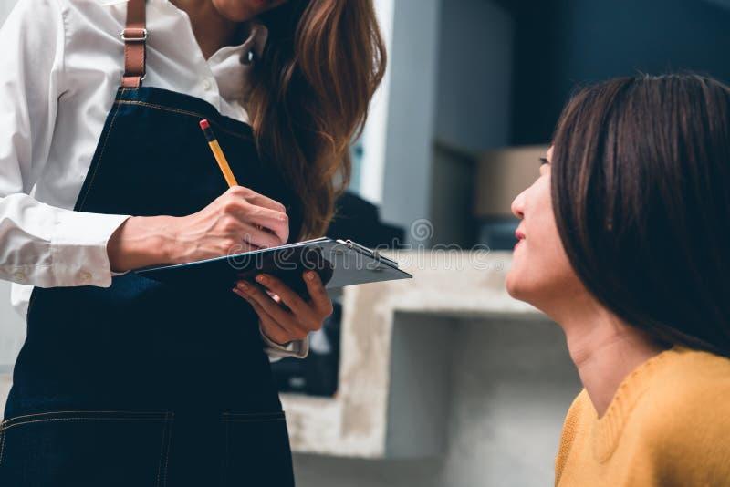 关闭接受从她的客户的年轻亚洲女性咖啡店所有者命令有在她的小咖啡馆的热烈欢迎微笑的 免版税库存照片