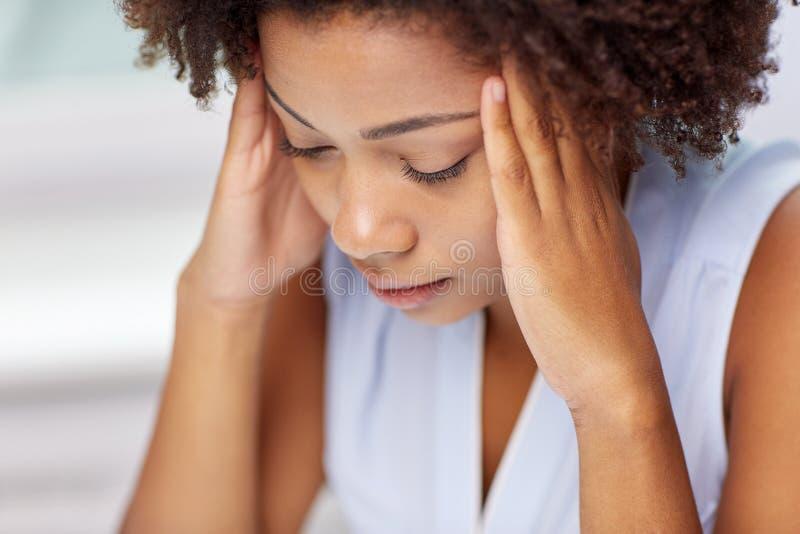 关闭接触她的头的非洲少妇 免版税图库摄影
