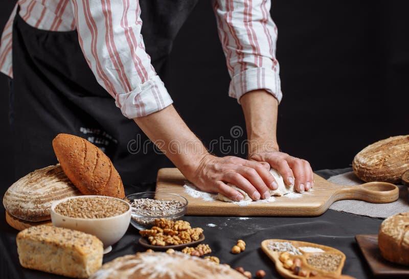 关闭揉面团和做与一根滚针的面包师手面包 免版税库存照片