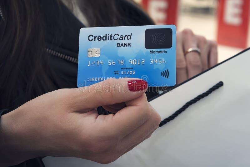 关闭握信用卡和购物带来的面孔女性手在购物中心背景 信用卡可读的细节  免版税库存图片
