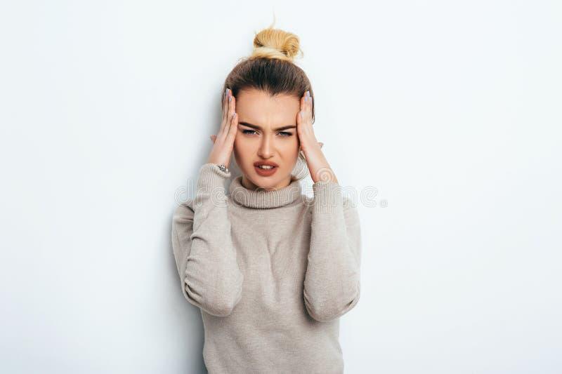 关闭握在头的年轻人被注重的恼怒的妇女被隔绝的画象手 消极人的情感,头疼面孔表示 免版税库存图片