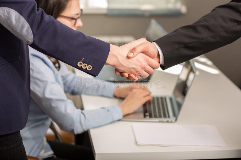 关闭握手协议项目的商人和合作在委员会会议期间在办公室 免版税库存图片
