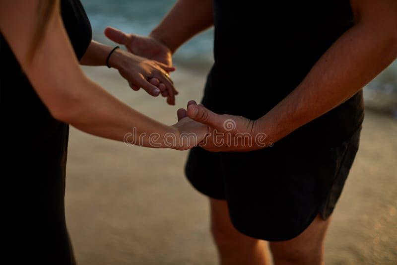 关闭握手的一对浪漫资深夫妇的背面图反对海在日落 免版税图库摄影