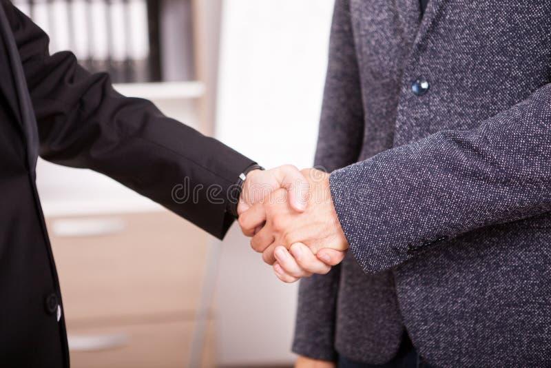 关闭握手的两个商务伙伴在办公室 免版税库存图片