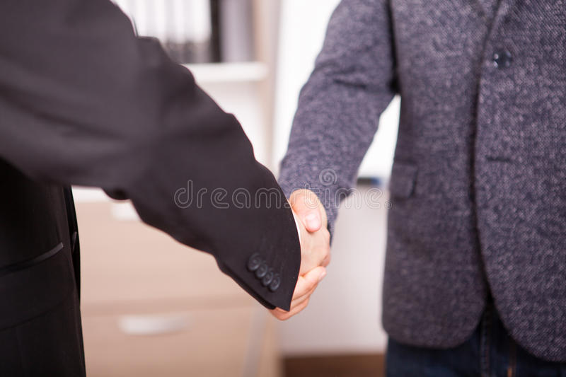 关闭握手的两个商务伙伴在办公室 免版税图库摄影
