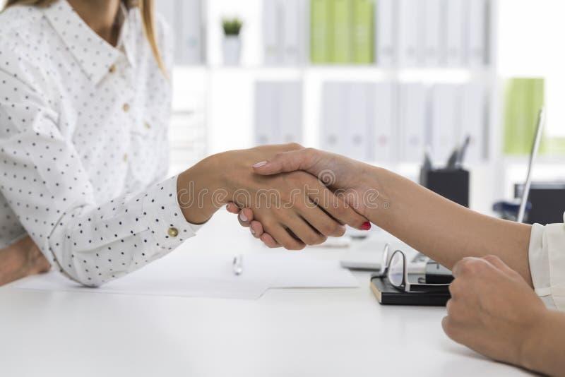 关闭握手的两个女性商务伙伴 库存照片