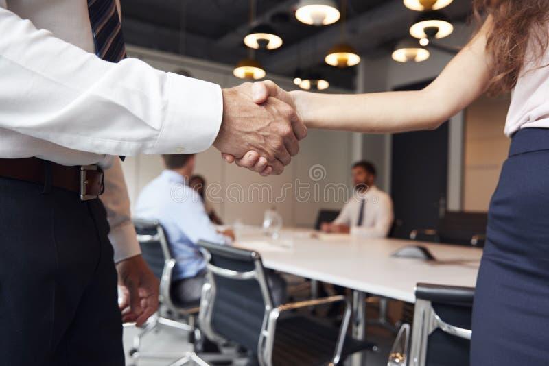 关闭握手的商人和女实业家在有见面在表附近的同事的现代会议室里在背景中 库存照片