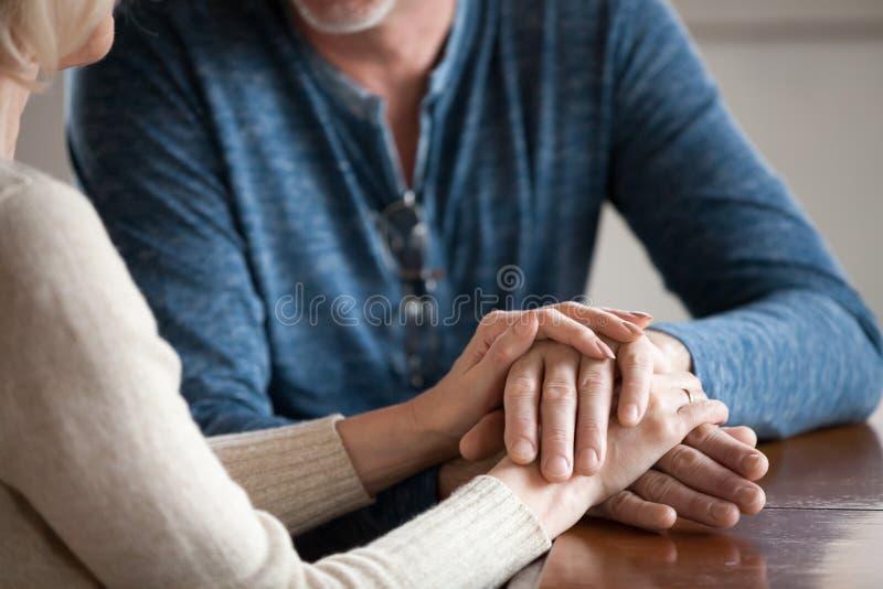 关闭握手的浪漫年迈的夫妇爱抚 免版税库存图片