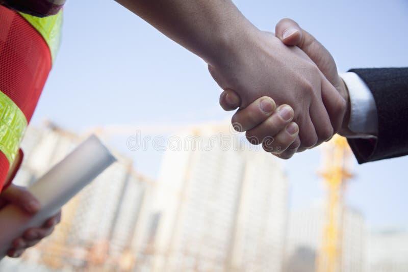 关闭握手的建筑师和建筑承包商 库存图片