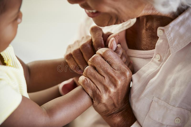 关闭握有小孙女的祖母手一起打比赛 库存图片