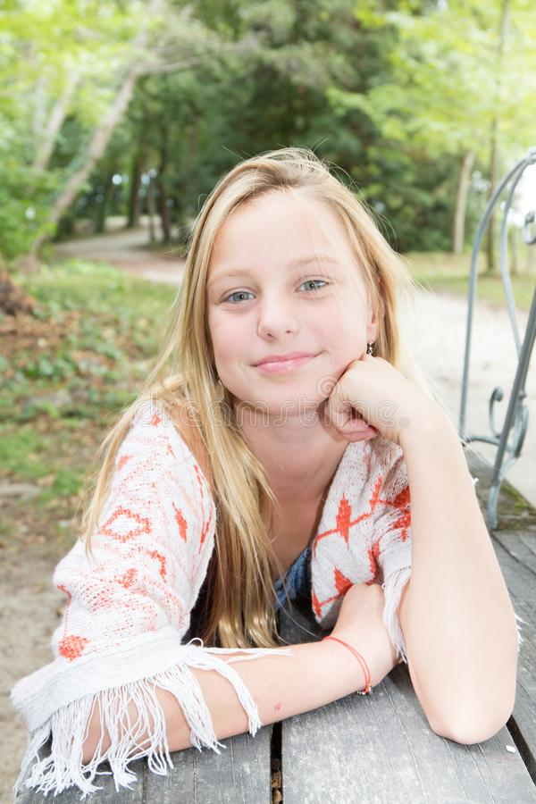 关闭摆在画象年轻美丽的白肤金发的女孩的少年户外 图库摄影