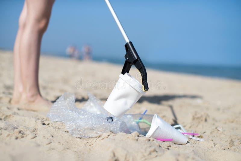 关闭收集塑料废物的人从被污染的海滩 免版税库存图片