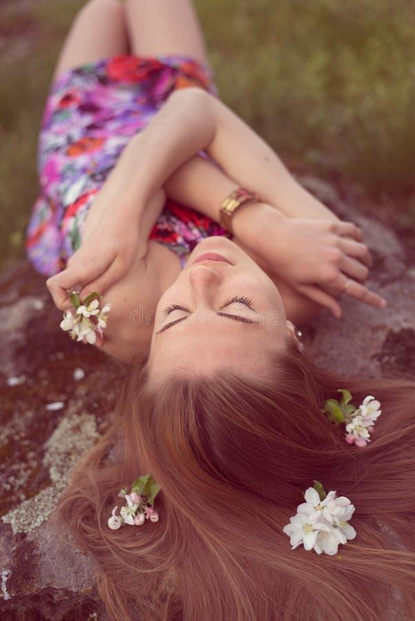 关闭放置在与花的石头的美丽的白肤金发的少妇画象在作梦她的头发闭合值的眼睛户外 免版税库存图片