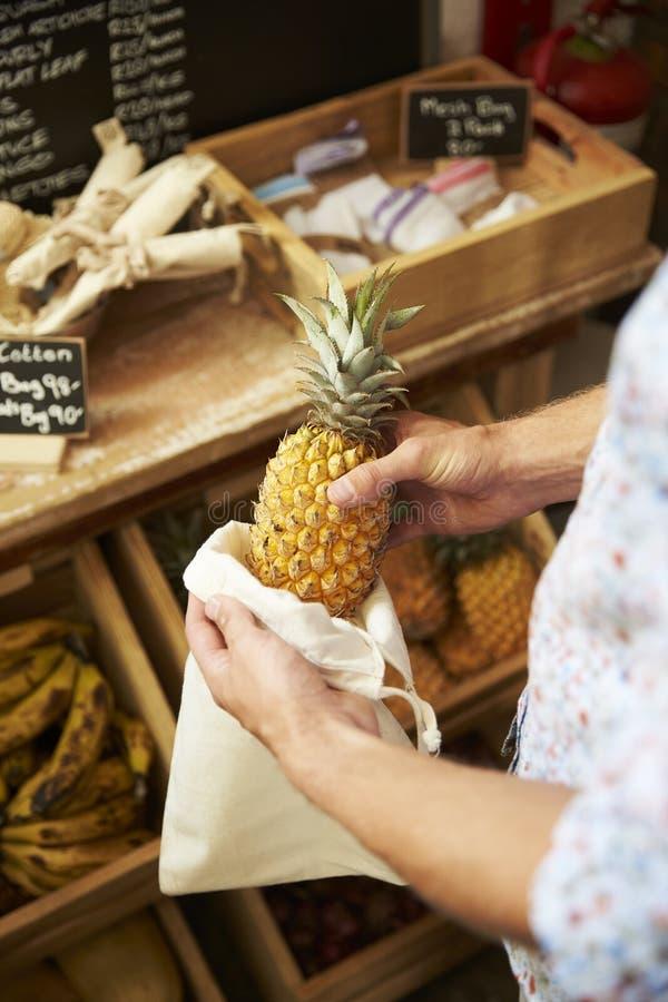 关闭放菠萝的人入可再用的棉花袋子在塑料自由杂货店 免版税库存照片