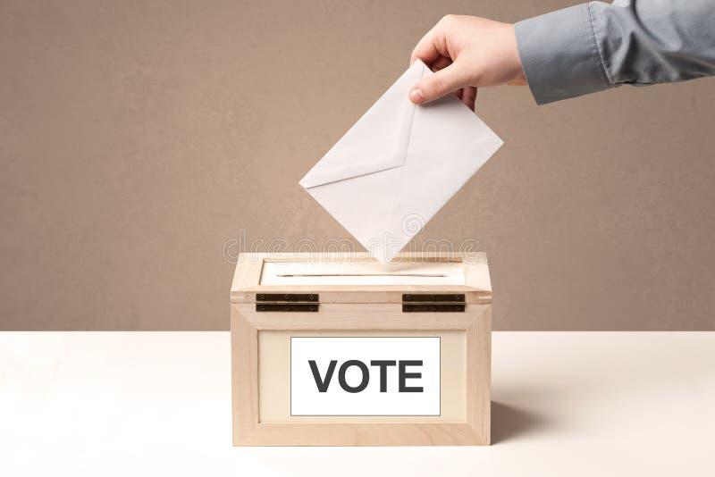 关闭放表决的男性手入投票箱 库存图片