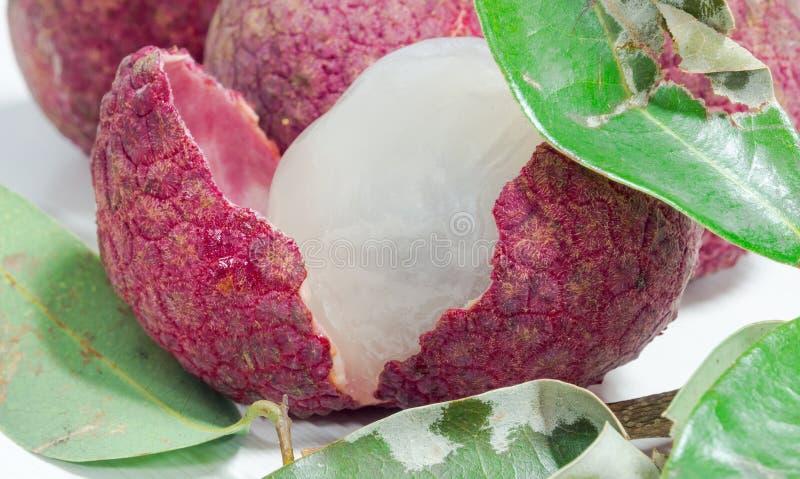 关闭新鲜的lychee和剥皮显示与绿色叶子的红色皮肤和白色骨肉 免版税图库摄影
