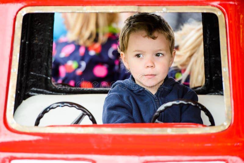 关闭旋转木马汽车的#2一个男孩 库存照片