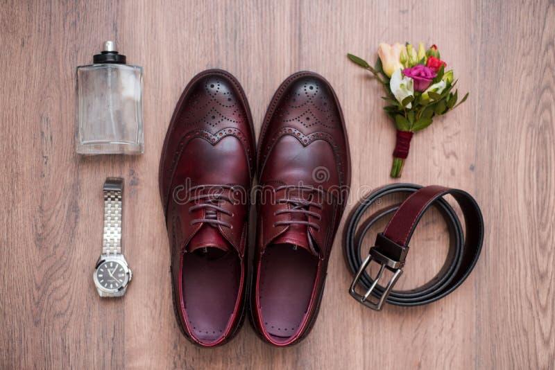 关闭时髦人士辅助部件 在白色木土气背景的黑bowtie、皮鞋、传送带和花钮扣眼上插的花 ?? 免版税库存照片