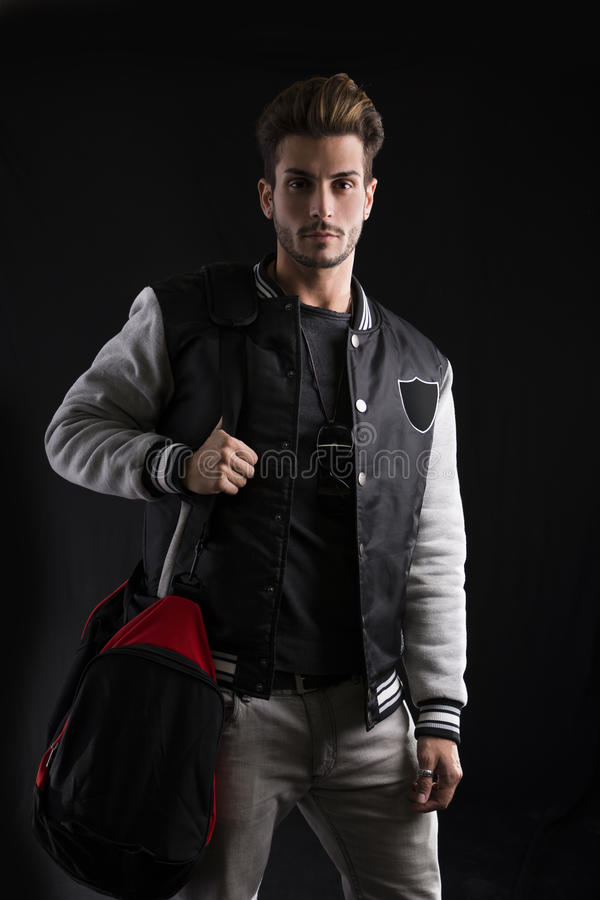 关闭时髦时尚成套装备佩带的大学夹克的华美的人有体育袋子的 库存图片