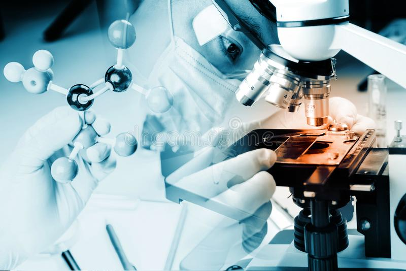 关闭显微镜与原子球的观察样品和研究的棍子分子模型,在实验室学会,运作,解答 免版税库存图片